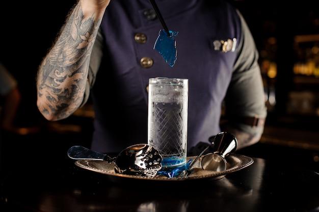 Barman versieren een cocktailglas met een blauw karamelvel