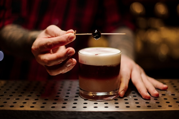 Barman versieren schilferige alcoholische zoete cocktail met een kers