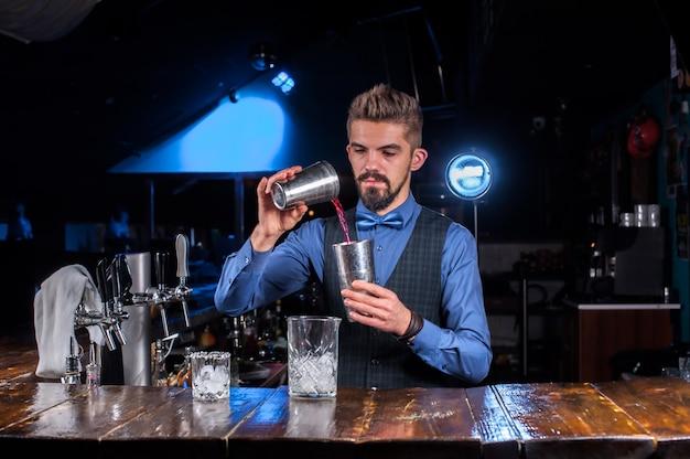 Barman verzint een cocktail achter de bar