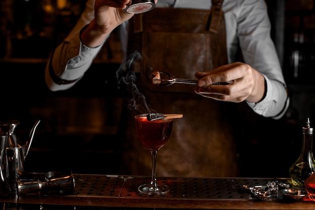Barman voeg kruiden toe voor een decor boven een heerlijke rode cocktail in het glas