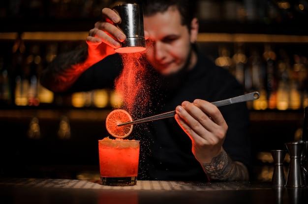 Barman voegt aan een alcoholische cocktail in het glas een gedroogde sinaasappel toe met een pincet en aromatisch poeder in het rode licht op de toog