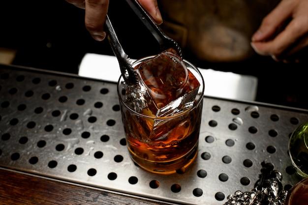 Barman voegt een ijsblokje in whisky toe