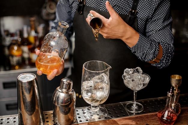 Barman voegt een portie siroop toe aan het grote cocktailglas
