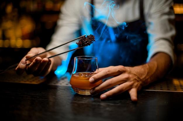 Barman voegt gekoelde smeltende karamel met twezzers toe aan het cocktailglas met ijsblokjes onder blauwe lichten