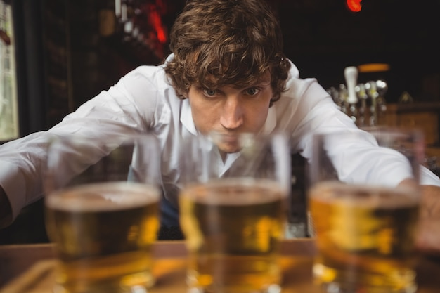 Barman voering whisky shot glazen op toog