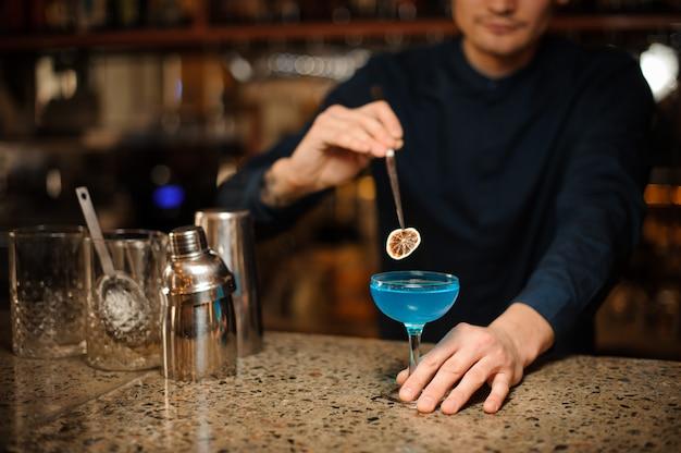 Barman vult de blue lagoon-alcoholcocktail aan met een plakje gedroogde citrusvruchten