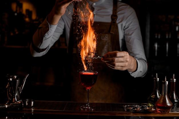 Barman vuur een decor voor een heerlijke rode cocktail in het glas