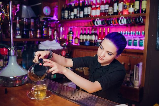 Barman werkt, cocktails bereidt. concept over service en dranken. meisje met blauw haar