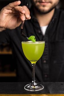 Barman zetten een garnering op een gele cocktail in een nick en nora glas.