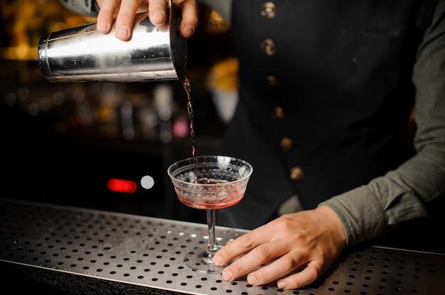 Barmanhand die alcoholische drank met campari gieten in het cocktailglas