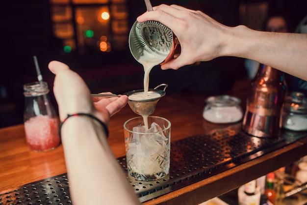 Barmanhand die een glas met de zomer lichtzure cocktail met roze perzikalcoholische drank houden die met bloem onder de barteller wordt verfraaid