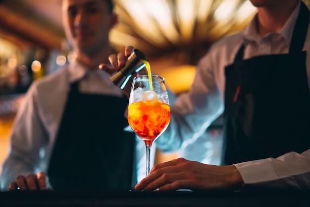 Barmanhand roeren een frisse en zoete sinaasappel zomercocktail met een lepel op de toog