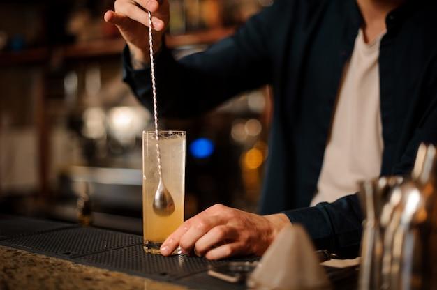 Barmanhand roert een frisse en zoete sinaasappel zomercocktail