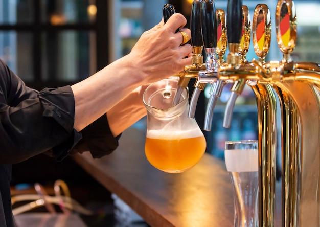 Barmanhanden die een lagerbierbier in een glas gieten