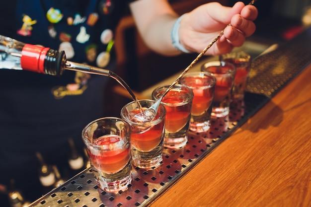 Barmanman die hete alcoholschoten op de bar in de bar met een professionele brander maken. de barman steekt een aansteker boven een glas aan. ontspan in de nachtclub. warm vuur drankjes. laat het feestje komen.