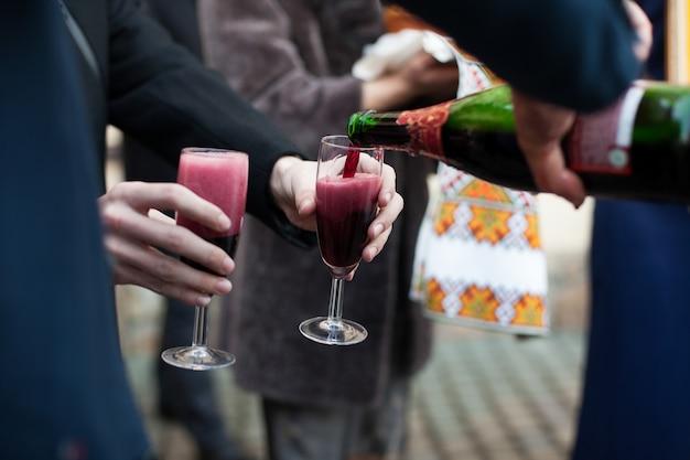 Barmannen die wijn in glazen voor bruidegom en gasten bij huwelijk gieten