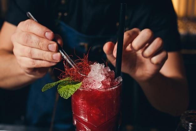 Barmannen handen sprenkelen het sap in het cocktailglas gevuld met alcoholische drank