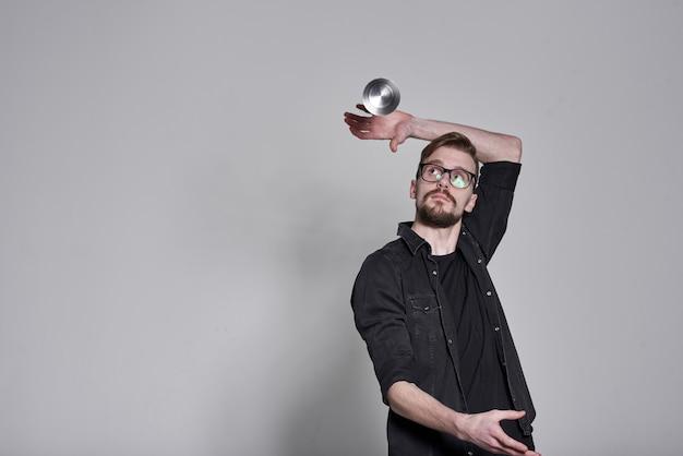Barmannen man jongleren flessen en schudden op witte muur, tweeling
