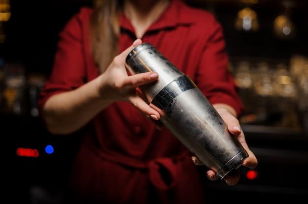 Barmannenmeisje die cocktail maken bij de barteller