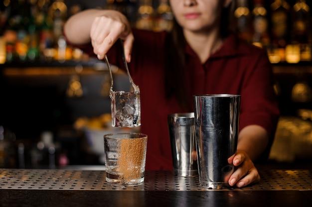 Barmannenmeisje die een groot ijsblokje in een leeg glas op een barteller zetten