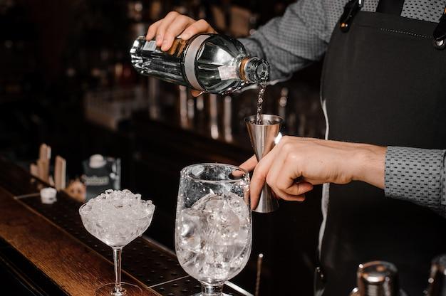 Barmans overhandigt gieten alcoholische drank in een jigger om een verse cocktail te bereiden