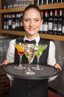 Barmeisje houden plaat met cocktails