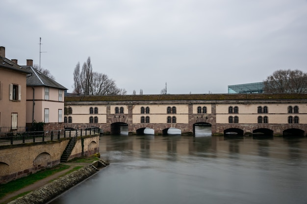 Barrage vauban omgeven door water en gebouwen onder een bewolkte hemel in straatsburg in frankrijk