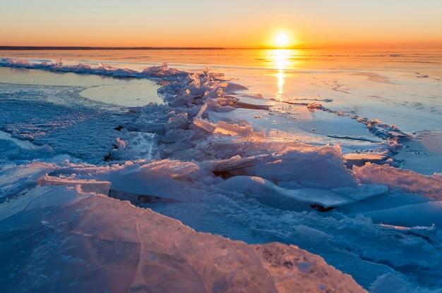 Barst in het ijs op een bevroren meer bij zonsondergang