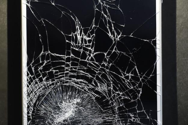 Barst op het glas. gebroken scherm. gebroken telefoon. gebarsten glas achtergrond. witte barsten in het glas.