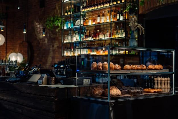 Barteller met een gebaksvitrine in klein restaurant flessen alcohol en sterke drank op achtergrondverlichting