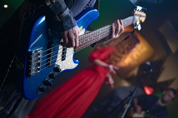 Basgitaar in de handen van een muzikant