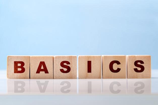 Basics woord geschreven op houtblokken op blauwe achtergrond. back to basics of vereenvoudigend bedrijfsconcept.