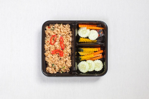 Basilicum gebakken rijst met kipgehakt, in een zwarte plastic doos gedaan, op een wit tafelkleed, voedseldoos, pittige gebakken kip met basilicumblaadjes, thais eten.