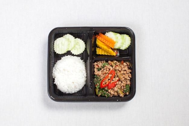 Basilicum gebakken rijst met varkensgehakt, in een zwarte plastic doos gedaan, op een wit tafelkleed, voedseldoos, pittig gebakken varkensvlees met basilicumbladeren, thais eten.