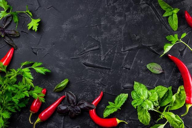 Basilicum, peterselie en rode peper op zwarte achtergrond - voedselachtergrond in zwarte kleur