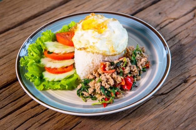Basilicum, varkensgehakt, gebakken ei, geserveerd met sla, komkommer, tomaat, schik een mooi gerecht, zet op een houten tafel.