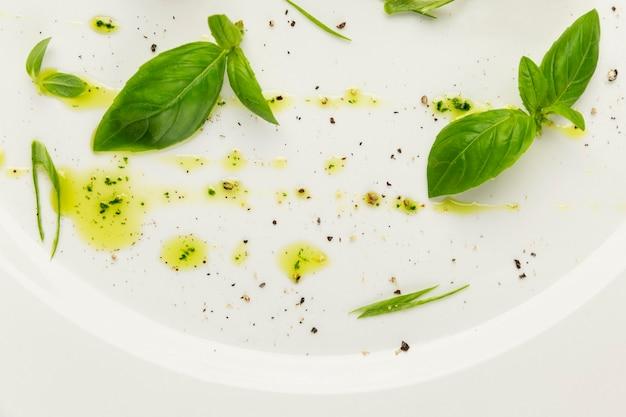 Basilicumbladeren en druppels olijfolie op een witte plaat. de kunst van de haute cuisine. detailopname.