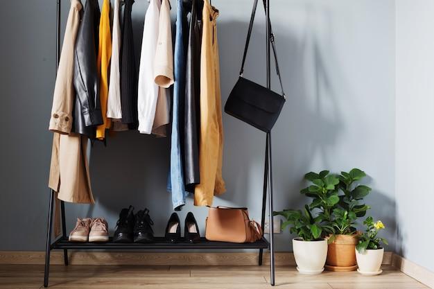 Basis herfstgarderobe voor dames met schoenen en handtassen op hanger