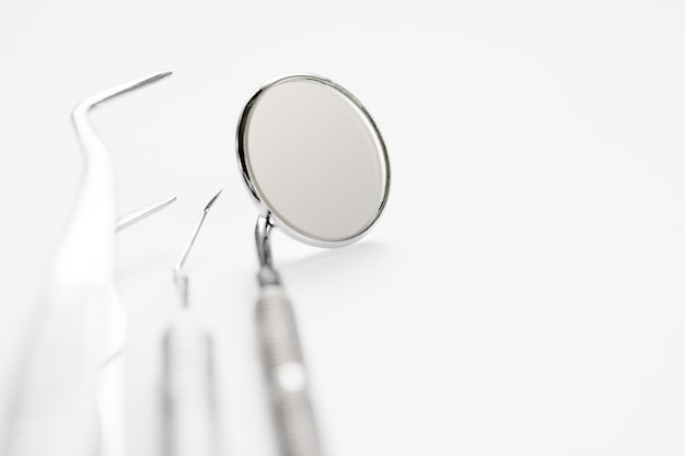 Basis tandartshulpmiddelen op witte achtergrond.