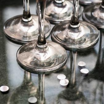 Basis van wijnglazen en zilveren confetti op reflecterend oppervlak