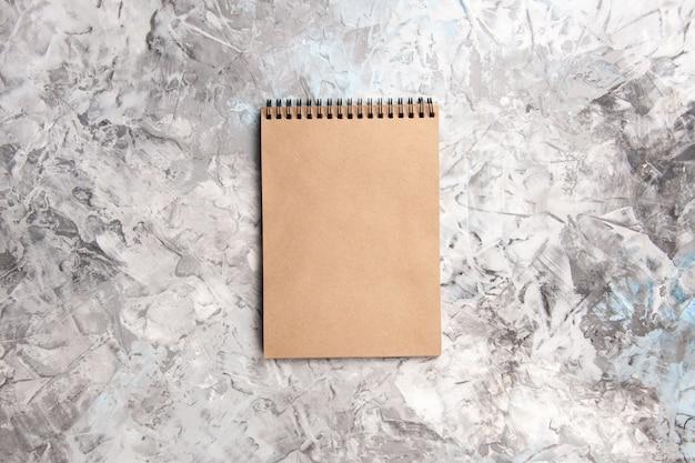 Basiskladblok in bovenaanzicht op notitieblok met witte tafel