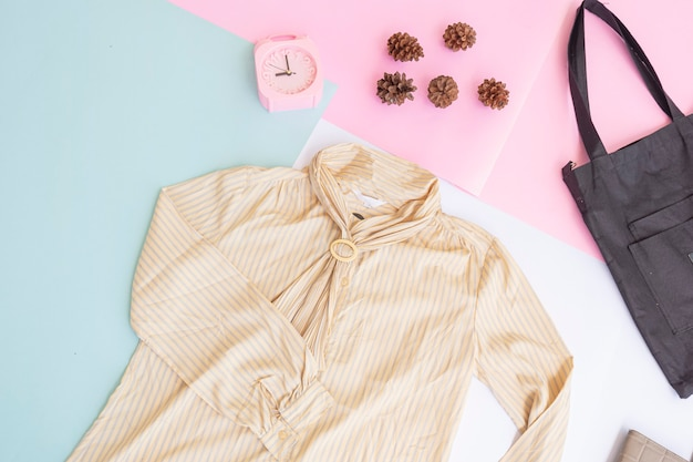 Basislay-out van dameskleding, overhemd op bleke mint pastel achtergrond. levensstijlconcept. wekker. handtas. tas