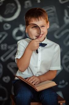 Basisschool student jongen met een vergrootglas in zijn handen