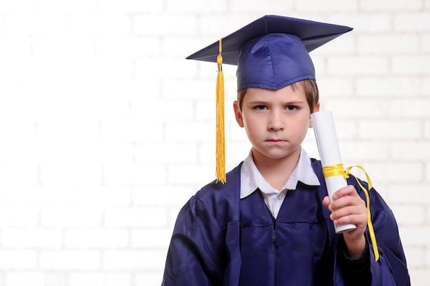 Basisschooljongen in kop en toga het stellen met diploma.