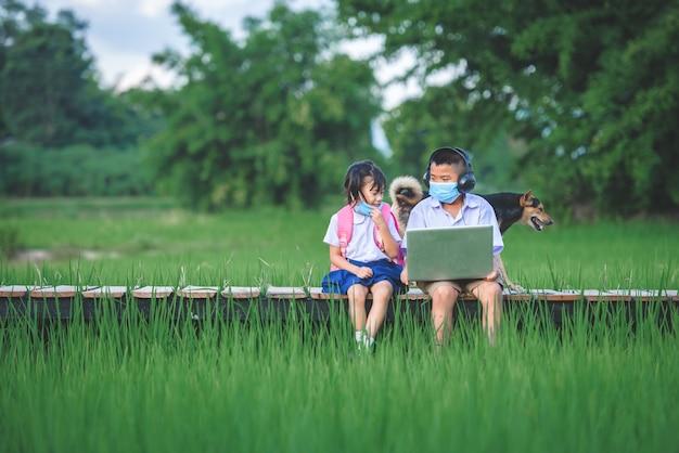 Basisschoolkinderen met een masker die laptop met behulp van