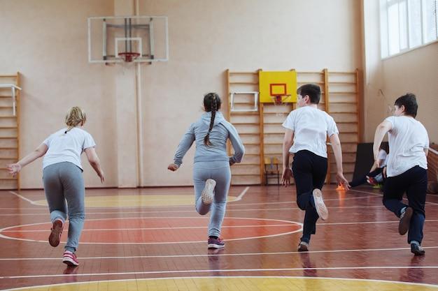 Basisschoolleerlingen een sportles binnenshuis. kinderen rennen en spelen mobiele spelletjes.