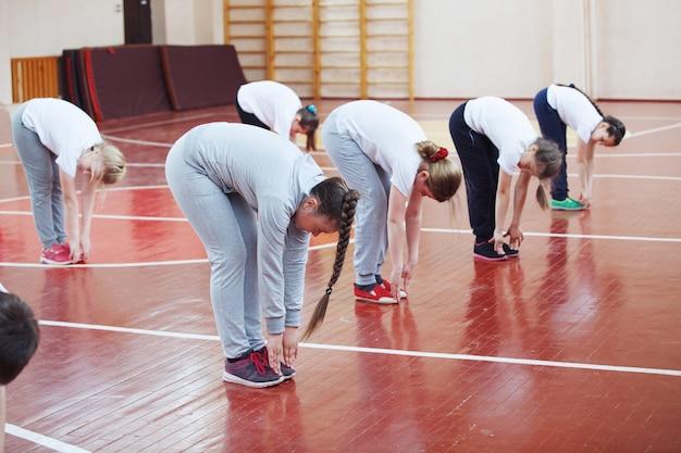 Basisschoolleerlingen een sportles binnenshuis. kinderen voeren gymnastische oefeningen uit.