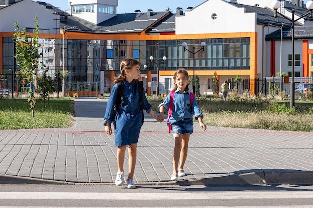 Basisschoolleerlingen gaan na schooltijd naar huis, de eerste schooldag, terug naar school.