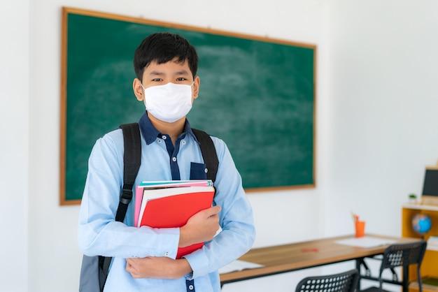 Basisschoolleerlingenjongen met rugzak en boeken die maskers dragen