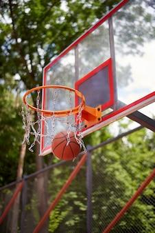 Basketbal dat de hoepel binnengaat